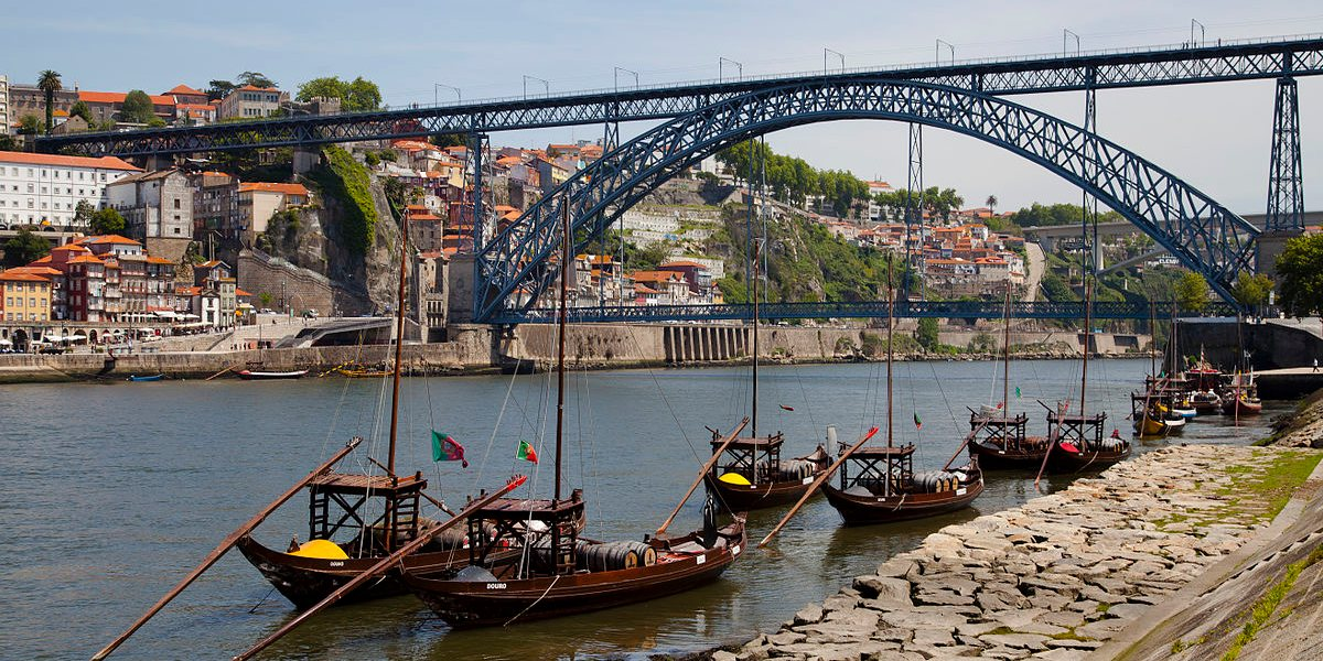 Best areas to stay in Porto - Vila Nova de Gaia riverside view of Dom Luís I bridge and rabelo boats